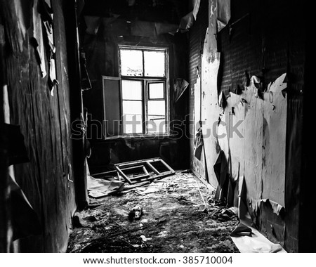 Black and white interior of burned house with white window - stock photo