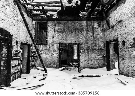 Black and white interior of burned house with white window snow - stock photo
