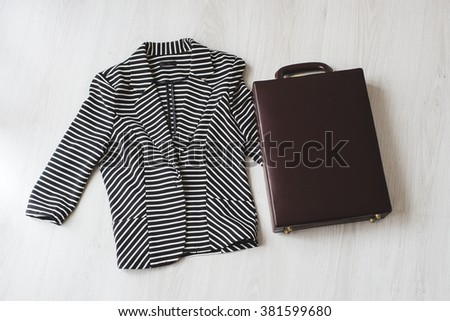Black and white jacket and brown suitcase on gray floor, top view for shopping concept. - stock photo