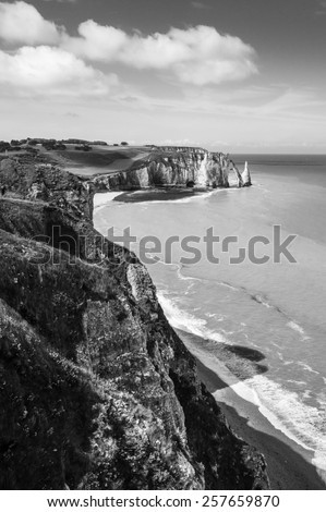 Black and white landscape: Etretat Aval cliff, rocks and natural arch landmark and blue ocean. Aerial view. Normandy, France, Europe. - stock photo