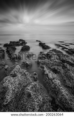 Black and white landscape looking out to sea with rocky coastline and beautiful sunset sky - stock photo