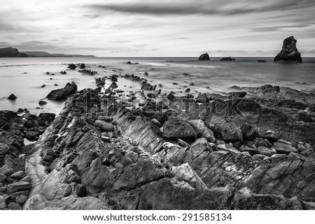 Black and white landscape of Mupe Bay with rocks in foreground - stock photo