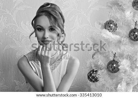 black and white lovely elegant woman posing in romantic christmas portrait with hair-style, make-up and happy expression near decorated xmas tree