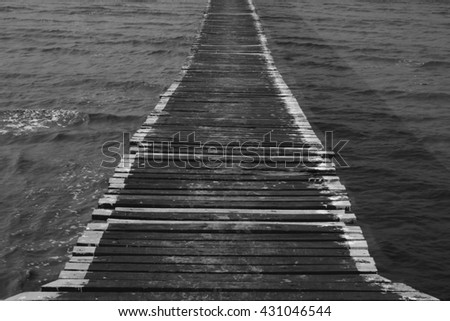 Black and white low-key concept. Old wooden bridge stretching into the sea. Choose a focal point at the lower center of the image.