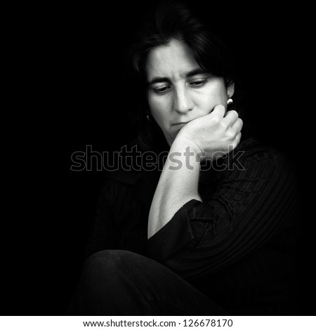 Black and white low key portrait of a beautiful and sad hispanic woman isolated on black - stock photo