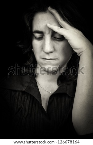 Black and white low key portrait of a beautiful and sad hispanic woman suffering a headache