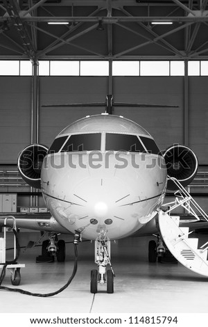 Black and White Luxury Business Private Jet in hangar - stock photo