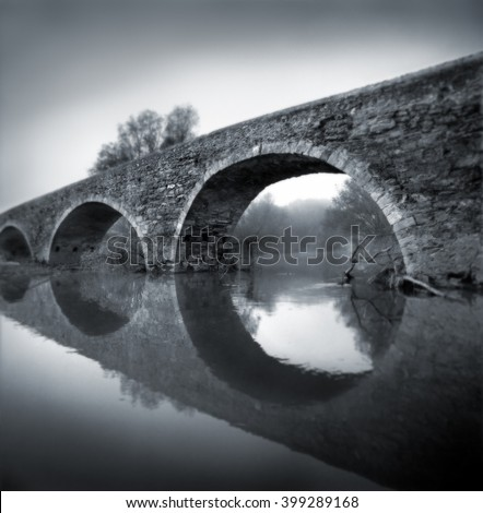 Black and white medium format film photographic shot. Romanesque bridge  at dawn in a misty environment - stock photo