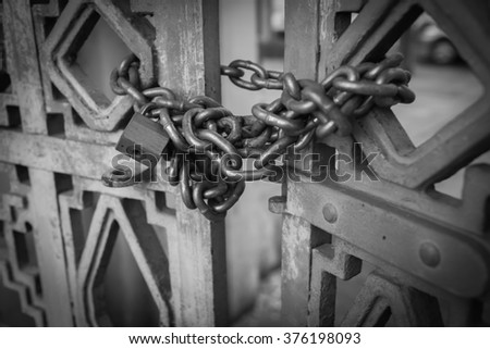 black and white metal padlock and chain on metal gate