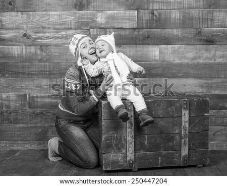 black and white, Mom and daughter smiling in multicolored studio interior - stock photo