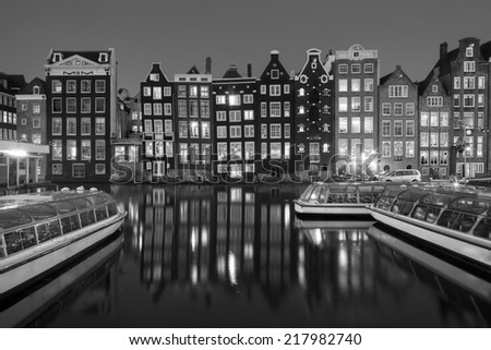 Black and white night shot of traditional houses in Amsterdam, capital of Holland, Netherlands,  with reflections in the canal - stock photo