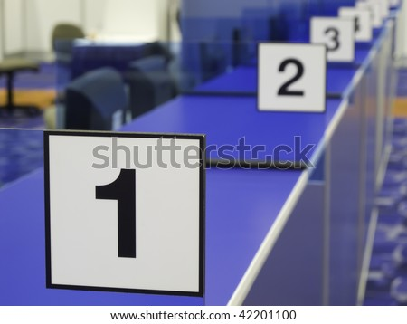 Black and white number signs along blue registration counter in convention hall (focus on 1)
