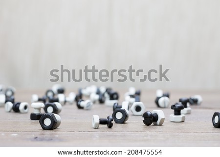 Black and white nuts and bolts on wooden desk - stock photo