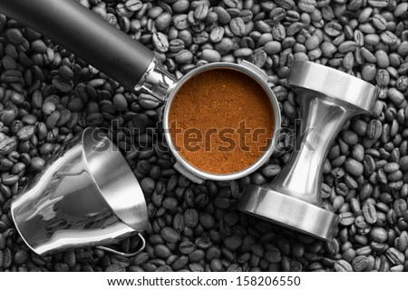 Black and white of a piston with grinder espresso (in color), a tamper and a stainless steel espresso cup on espresso beans.  - stock photo