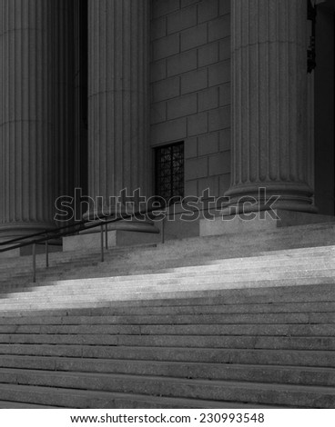 Black and white of a stairway with a band of sunlight shining across it with columns in the back.  This was taken in Washington DC. - stock photo