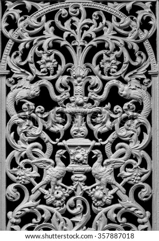 Black and white of an old forged decorative iron railing decorated by ornamenton a door - stock photo