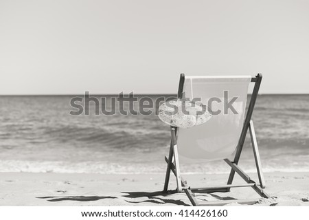 Black and white of deckchair and female hat on stunning tropical beach vacation background. Happy time - stock photo