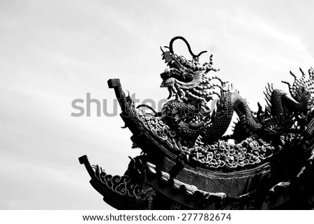 black and white of dragon stucco on the rooftop - stock photo