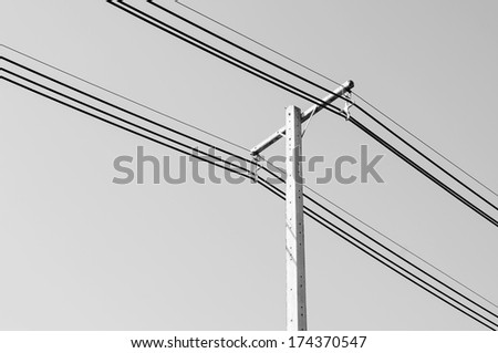 Black and white of electric power post with wire on sky background