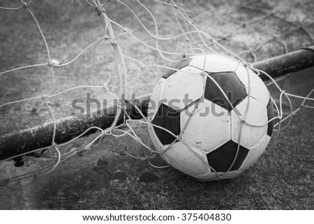 black and white old ball in the goal net  - stock photo