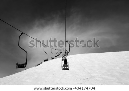 Black and white old chair-lift in ski resort. Caucasus Mountains, Elbrus region, mount Cheget. - stock photo