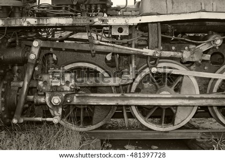 Black and white. Old, vintage locomotive which stands on the rails. Rusty and dirty train wheels close up. The train made in the distant past.