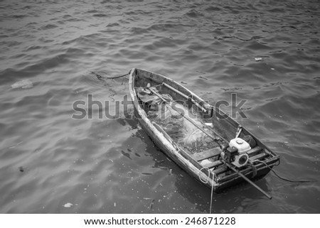 Black and white: old wooden fishing boat landing on the beach - stock photo