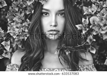 Black and white outdoor fashion photo of beautiful young woman surrounded by flowers spring blossom