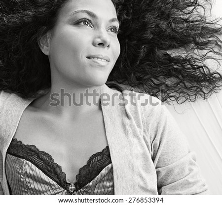 Black and white overhead portrait of a beautiful young exotic woman laying relaxing on a bed, smiling wearing sexy lingerie, interior space. Healthy well being aspirational lifestyle, bedroom indoors.