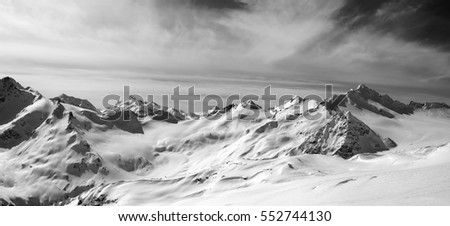 Black and white panorama of Caucasus Mountains in snow winter evening. Elbrus Region. View from off-piste slope of Elbrus.