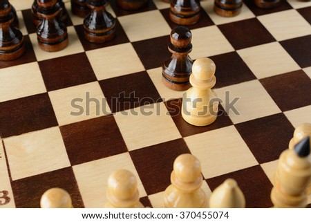 Black and white pawns facing each other on a chessboard
