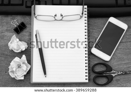 Black and white pen and glasses on notebook - stock photo