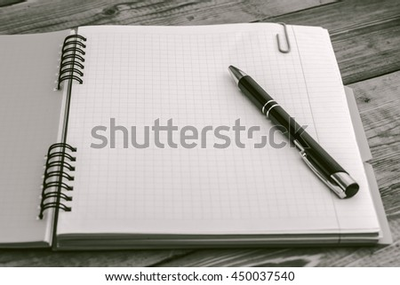 Black and White, pen on the closed notebook lying on a wooden table - stock photo
