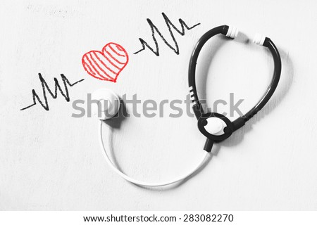 black and white phot of toy stethoscope and colorful heart beats illustration over textured background - stock photo