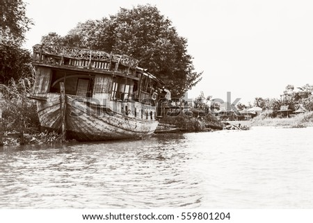 Black and white photo add texture vintage style of the old damaged wooden boat beached on the waterfront for background in Phra Nakhon Si Ayutthaya Province, Thailand