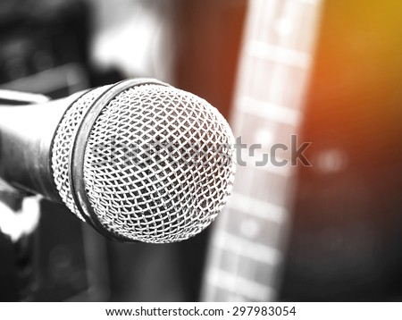 Black and white photo and lighting of the microphone in a recording studio or concert hall with electric guitar in out of focus background. : Vintage style and filtered process. - stock photo