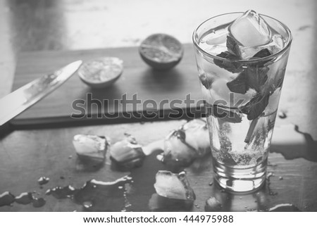 black and white photo. Homemade mojito cocktail, alcoholic or non-alcoholic cocktail on an old brown wooden background, closeup