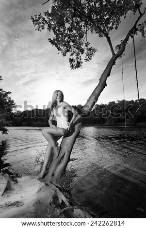 Black and white photo of a beautiful sexy blonde is posing in jeans shorts on the background of the river and the setting sun