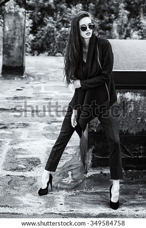 Black-and-white photo of a fashion female model alluring outdoor. City style. Fashion photo.  - stock photo