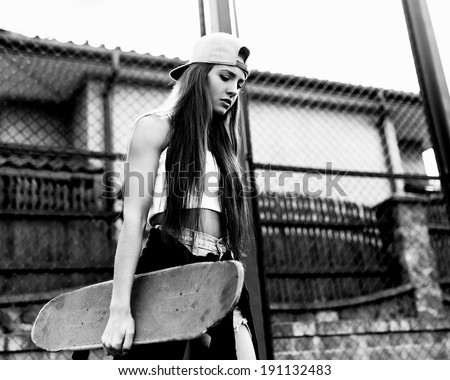 Black and white photo of a girl with skateboard against the sun