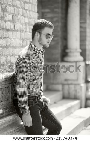 Black and white photo of a handsome young man wearing a shirt and jeans. Street shooting in Timisoara, Romania