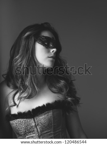 Black and white photo of a sexy young masked woman - stock photo