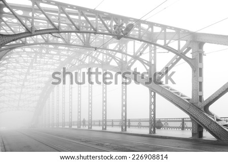 Black and white photo of a steel bridge over a river in fog, Cracow, Poland - stock photo