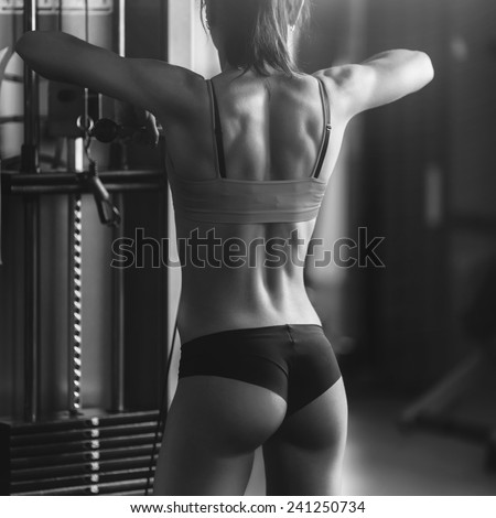Black and white photo of a strong woman. Brunette sexy fitness girl in sport wear with perfect body in the gym posing before training set - stock photo
