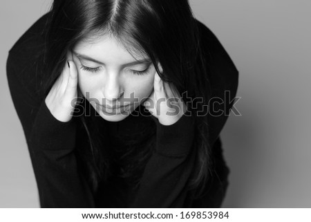Black and white photo of a thoughtful young woman with hands over her head - stock photo