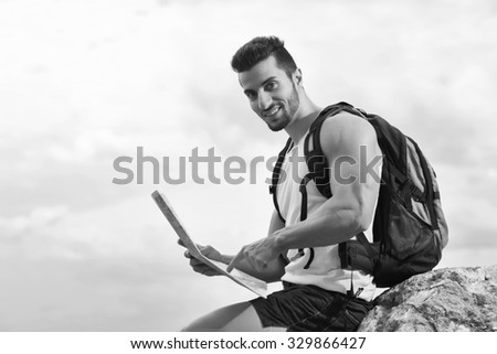 Black and white photo of a tourist with backpack standing on top of the mountain holding a map. Man with map exploring wilderness on trekking adventure. Tourist on the background of the sky