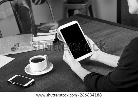Black and white photo of a woman holding a tablet with a no name coffee cup and a stack of books in background on a wood table with shallow depth of field - stock photo