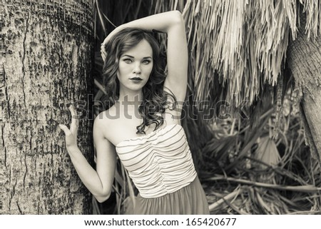 Black and white photo of a young model posing next to a palm tree