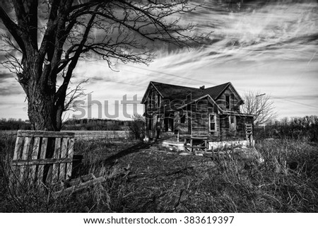 Black and white photo of an old scary abandoned farm house that is deteriorating with time and neglect.