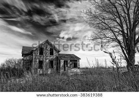 Black and white photo of an old scary abandoned farm house that is deteriorating with time with an old tree and a hangman's noose topped off with a dramatic dark sky.